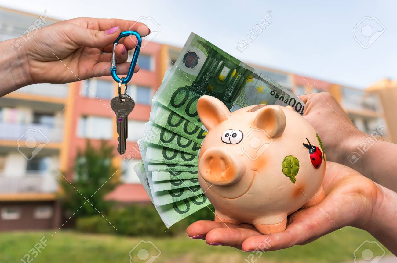 Real estate agent giving house keys to a new property owner, who is paying by euro money from piggy bank on blurred background Stock Photo - 73525479