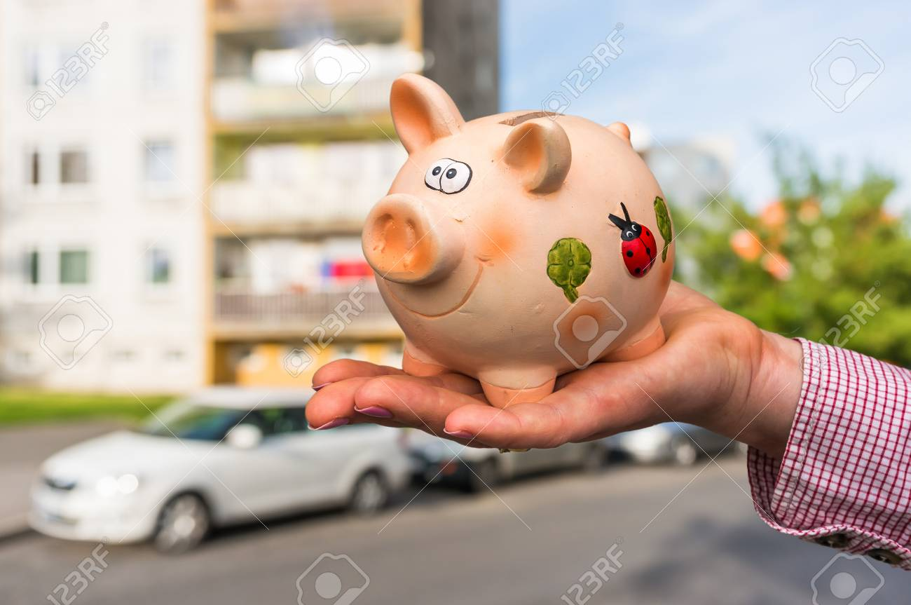 All savings money from pink ceramic piggy bank to pay for the dream home on blurred background Stock Photo - 73494484