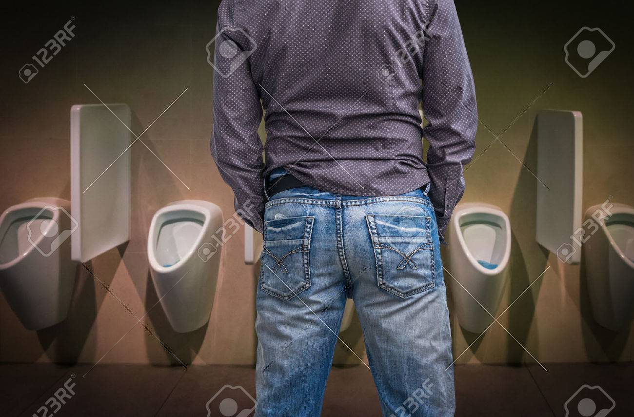 Standing man peeing to a urinal in restroom or incontinence concept Stock Photo - 73526707