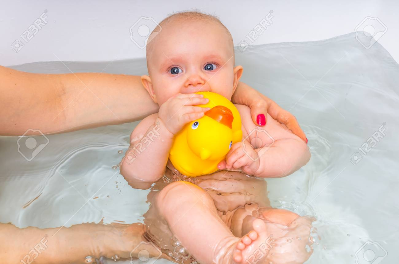 Smiling Newborn Baby Girl Bathing And Playing With Yellow Rubber ...