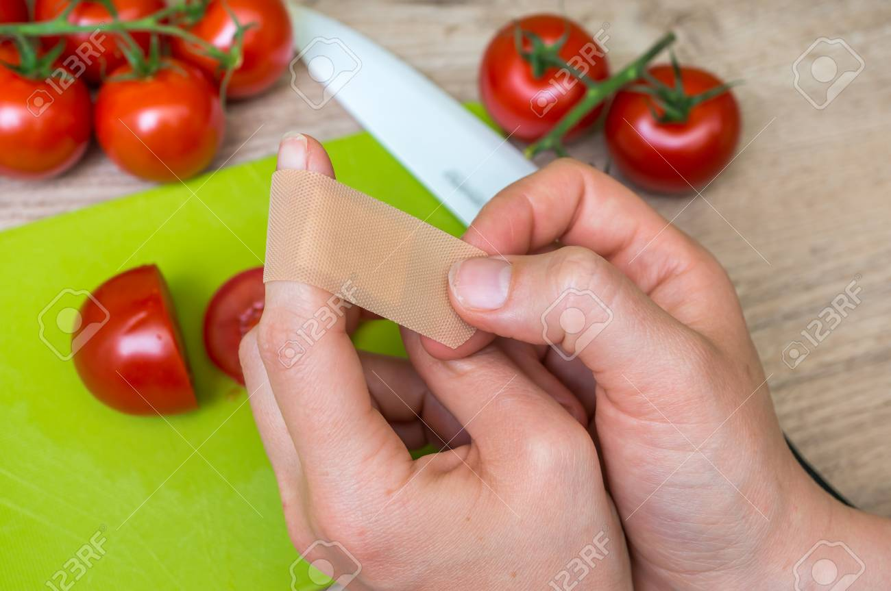 Young woman apply plaster on her finger - injury in kitchen - 80650342