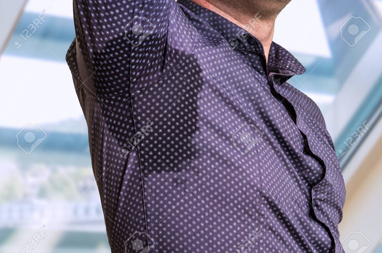 Young man with sweating under armpit in business office - 87669077