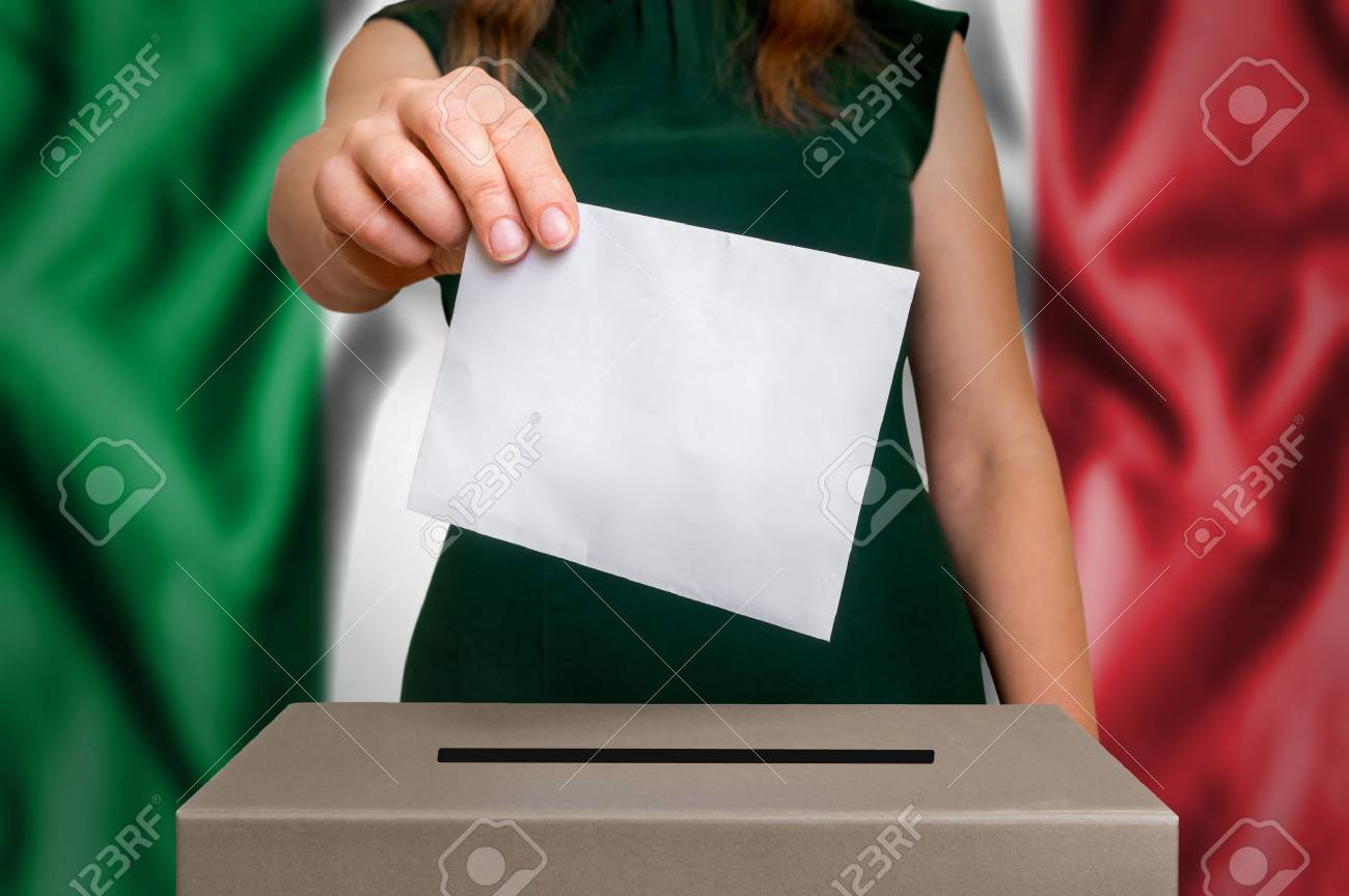 Election in Italy - voting at the ballot box. The hand of woman putting her vote in the ballot box. Flag of Italy on background. - 88075288
