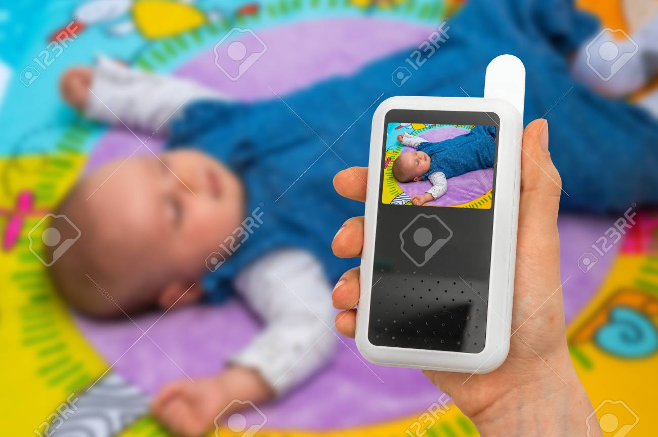 Hand of mother is holding baby monitor camera for safety of her cute baby - 89877759
