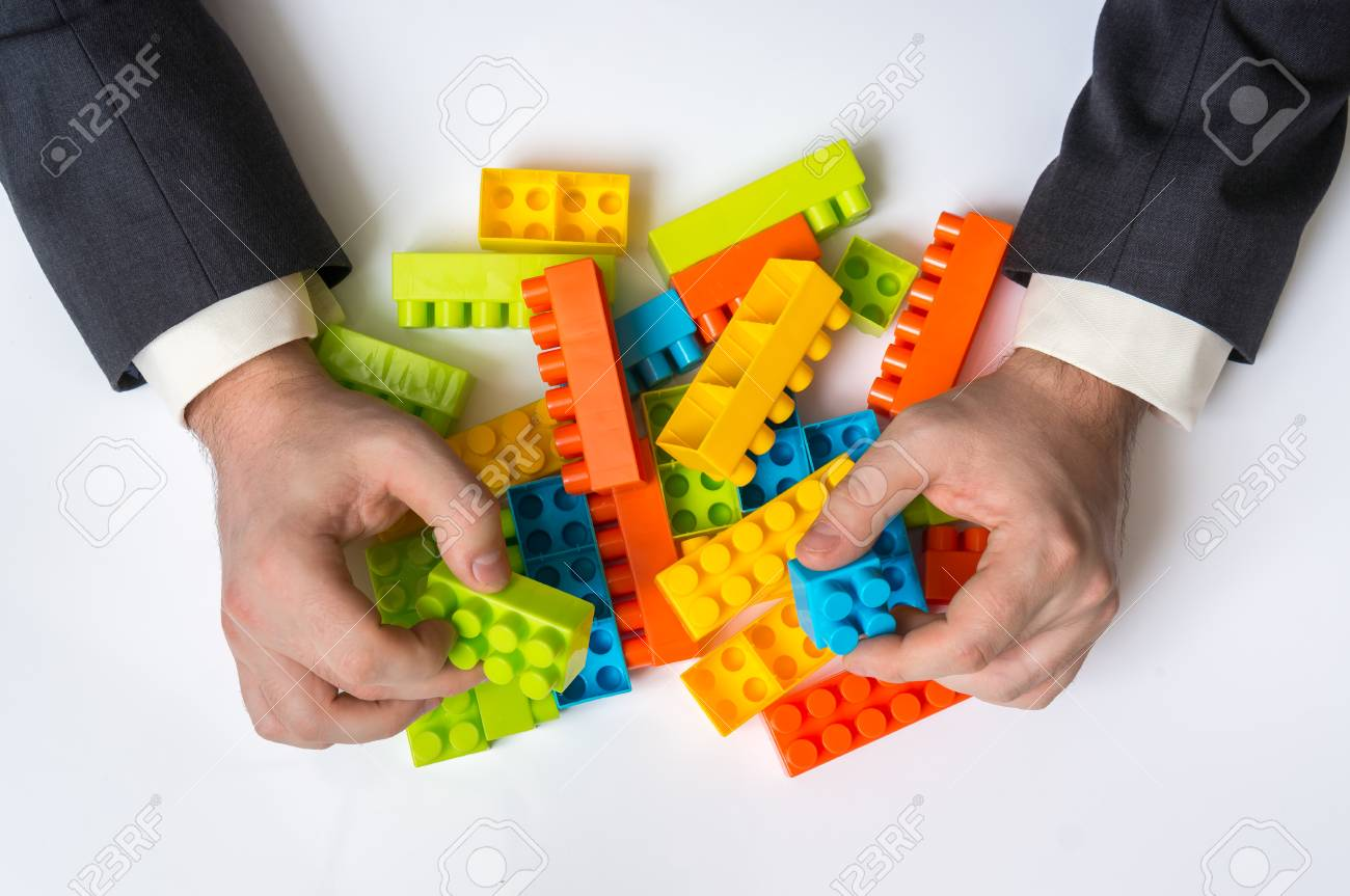 Concept of strategy and reorganization business ideas - young businessman playing with colored toy blocks - 94390966