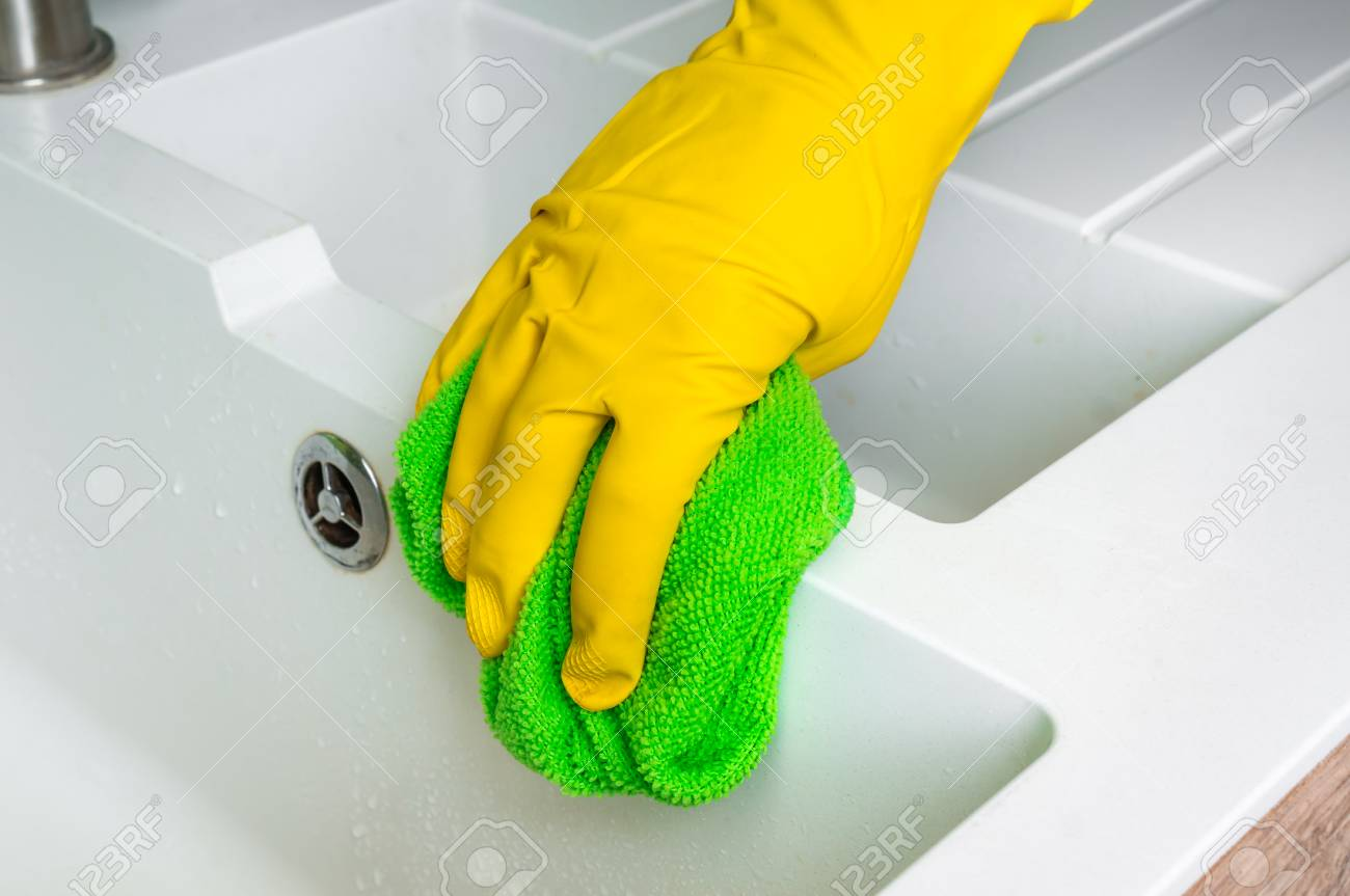 3d2301a9ff3f4 Hand in glove with green rag is wiping sink in kitchen - housework and housekeeping  concept