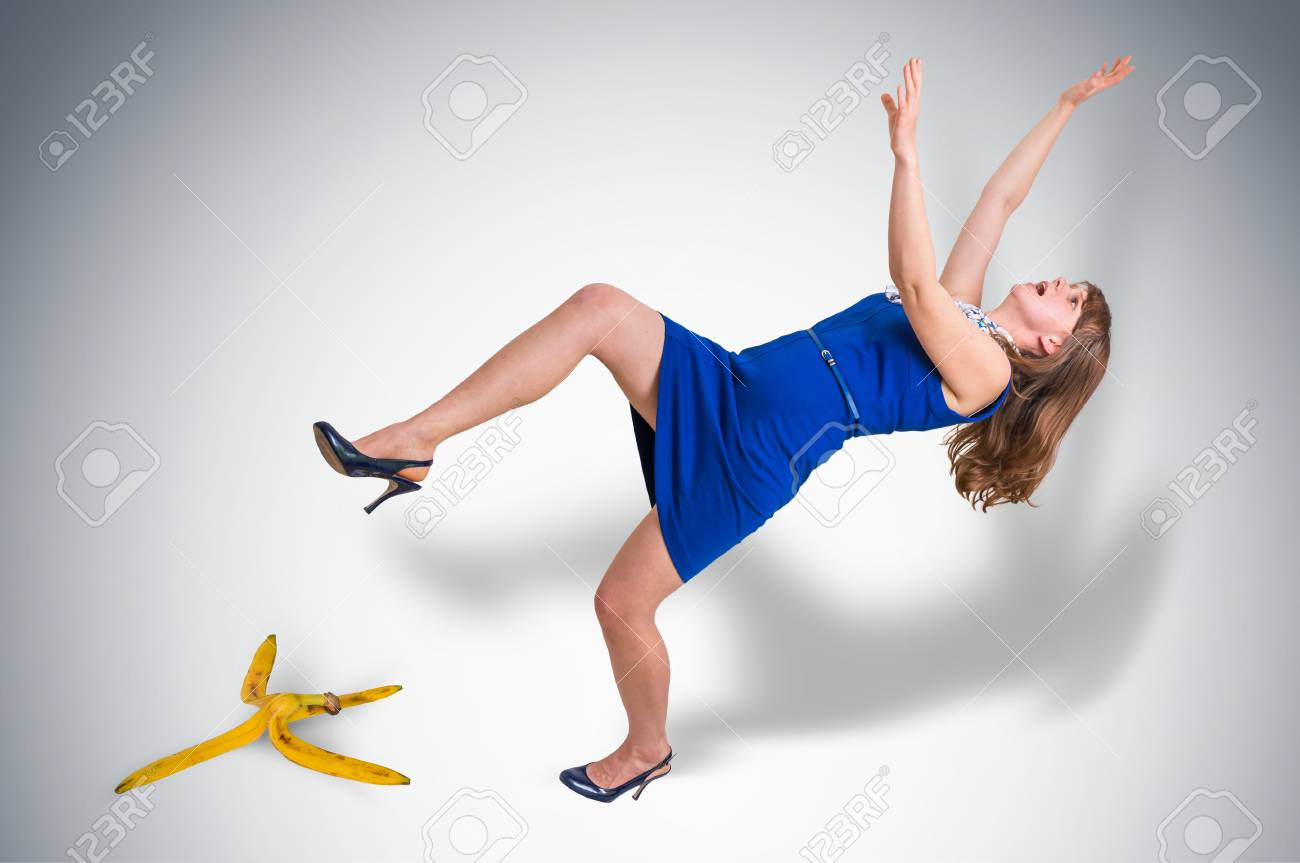 Business woman slipping and falling from a banana peel - business risk concept - 100035151