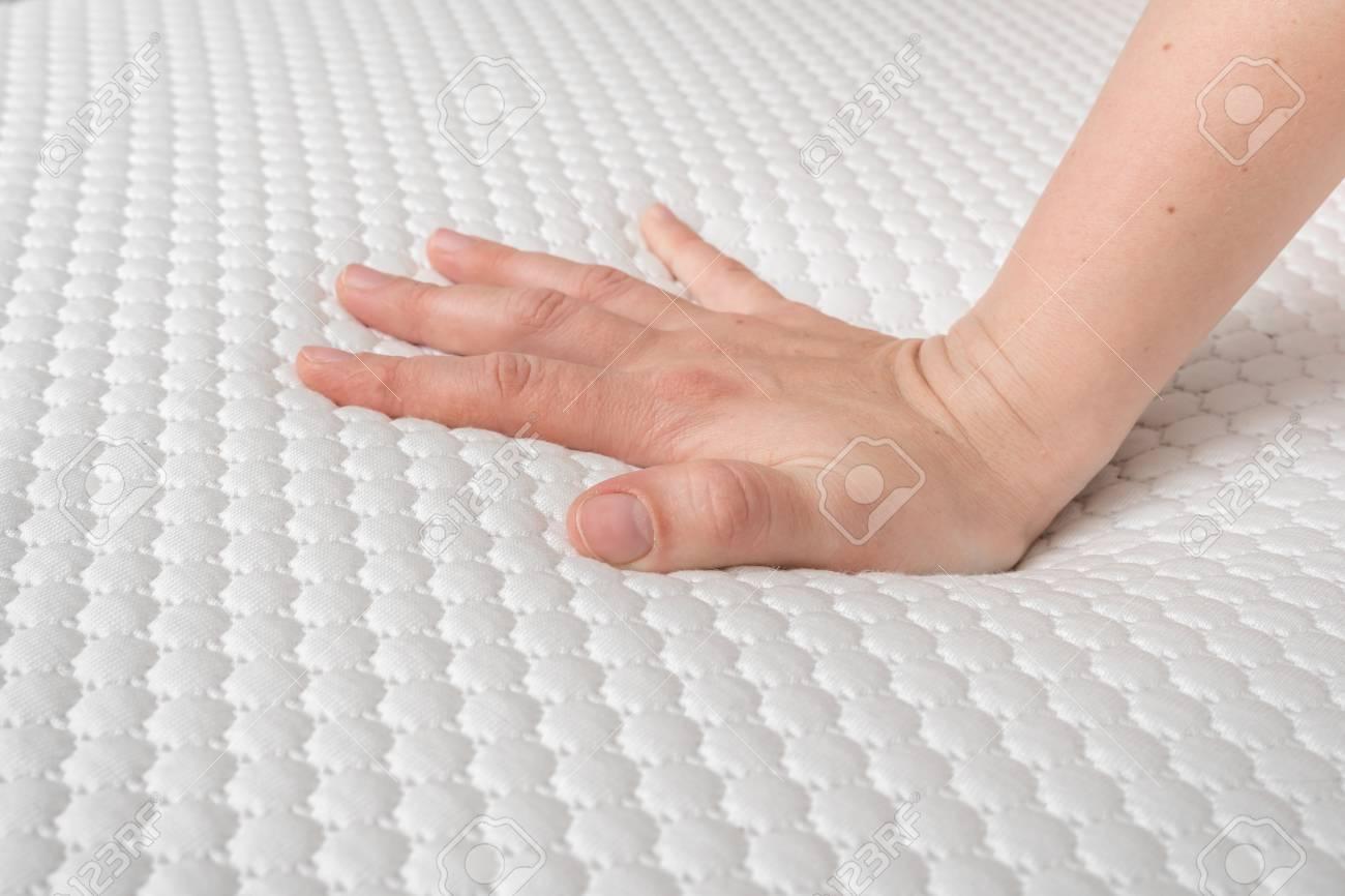 Woman is choosing new mattress for good sleeping. Hand of woman is testing mattress quality. - 122661557