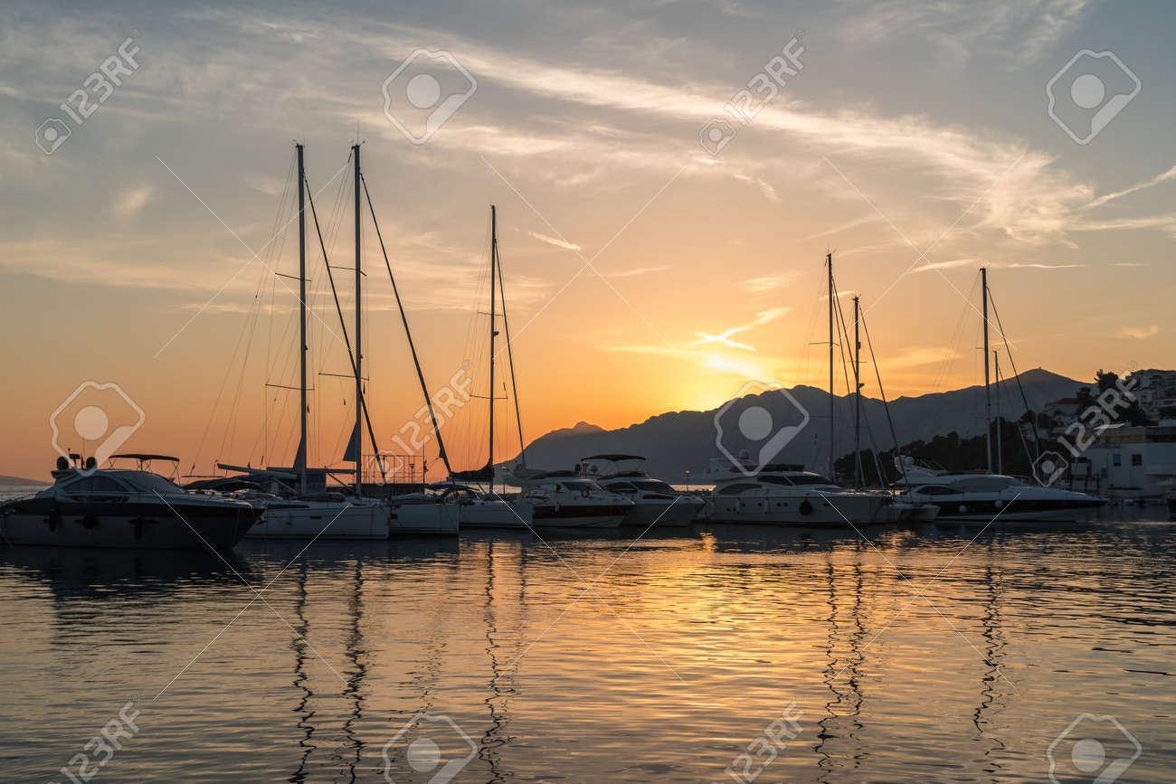 Beautiful sunset in Baska Voda town with Adriatic Sea and boats, Croatia - 127157620