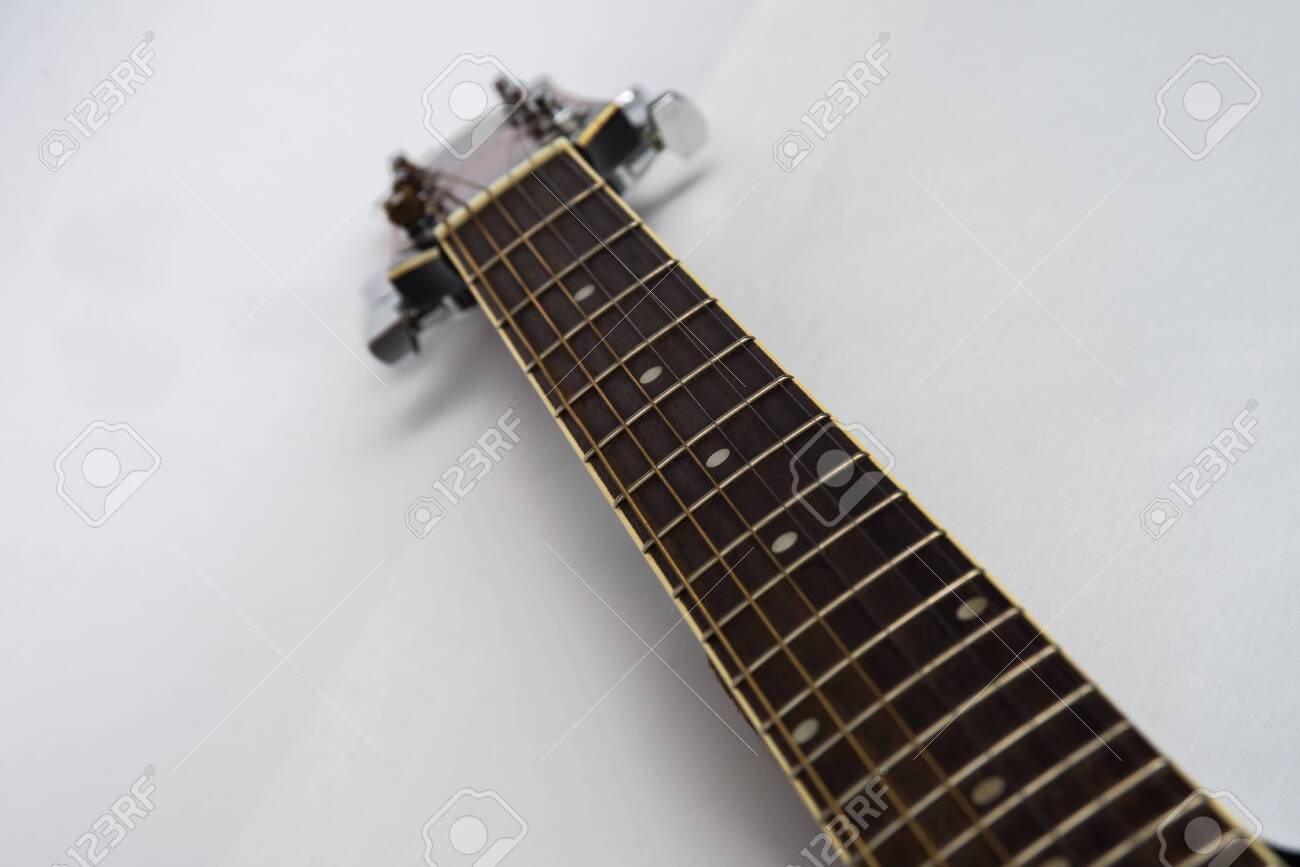 Guitar fretboard close-up top view of the neck of the guitar and strings on white isolated background. Acoustic guitar perspective along fretboard - 129308560