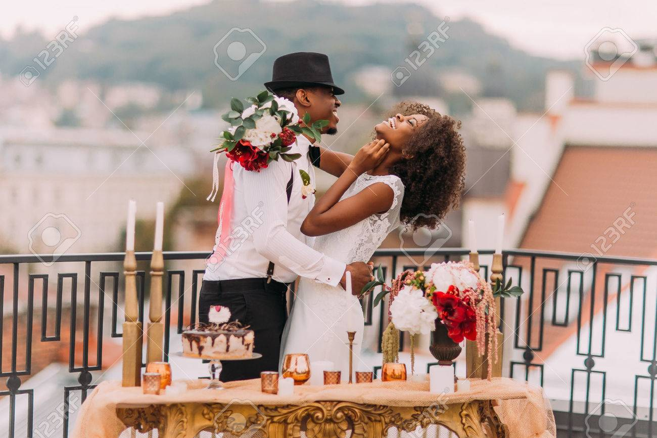 Stylish african wedding couple having fun on the balcony with luxury golden table in oriental style on foreground. - 53223970
