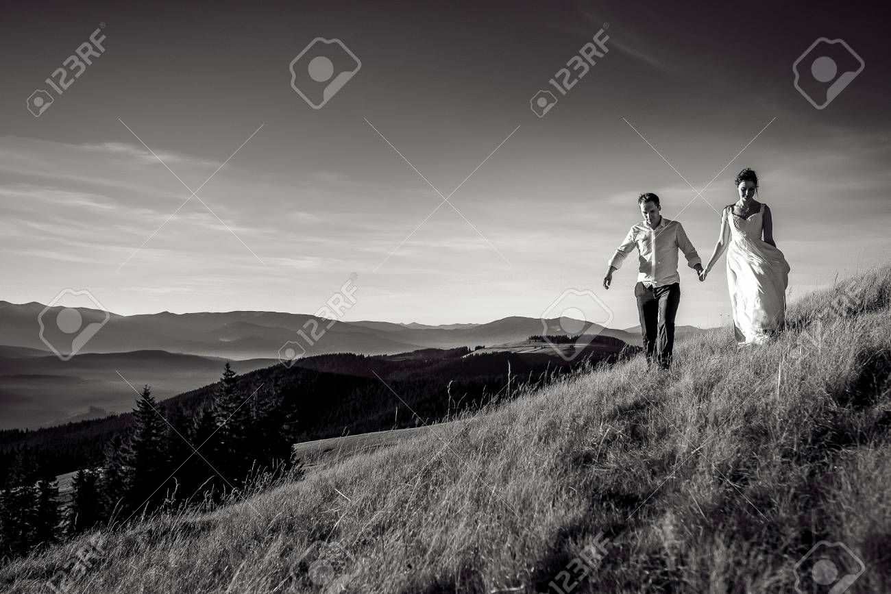 Romantic wedding couple walking in the mountains black and white photo stock photo