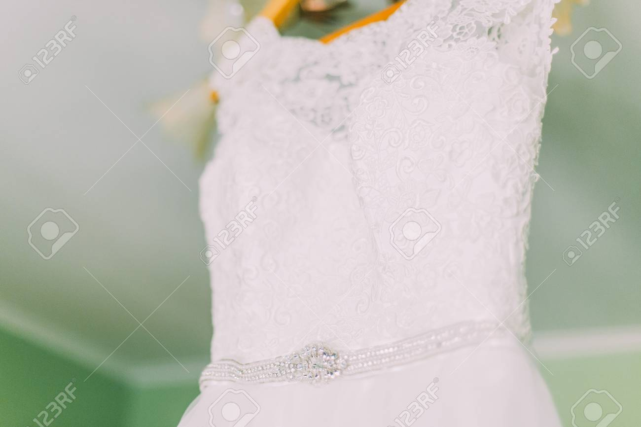 9b0fcaf81 Closeup photo of beautiful wedding dress on a hanger in a loft space.