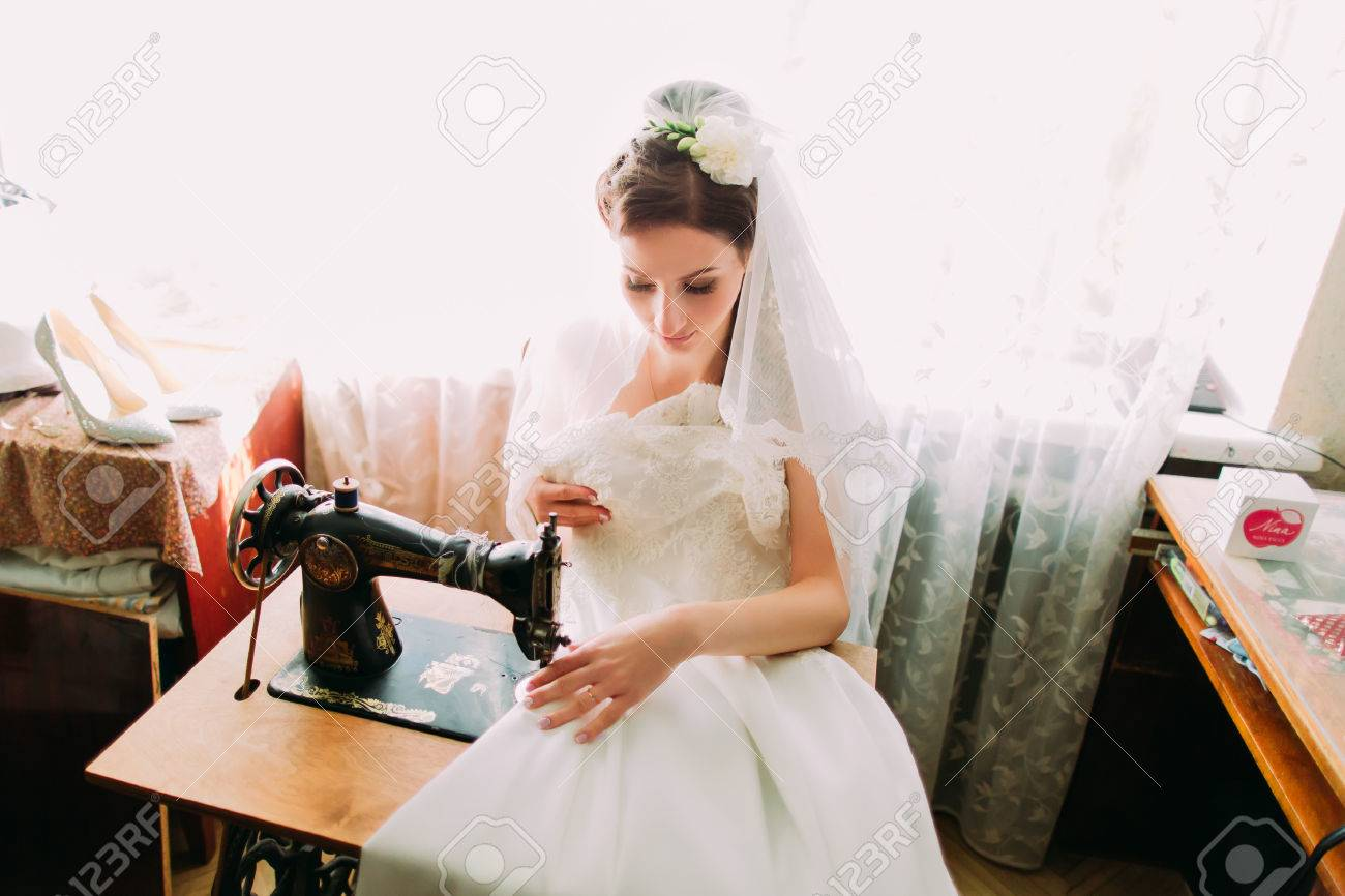 Beautiful Young Bride Makes Last Minute Adjustments To Her Wedding Dress At  An Ancient Old Treadle