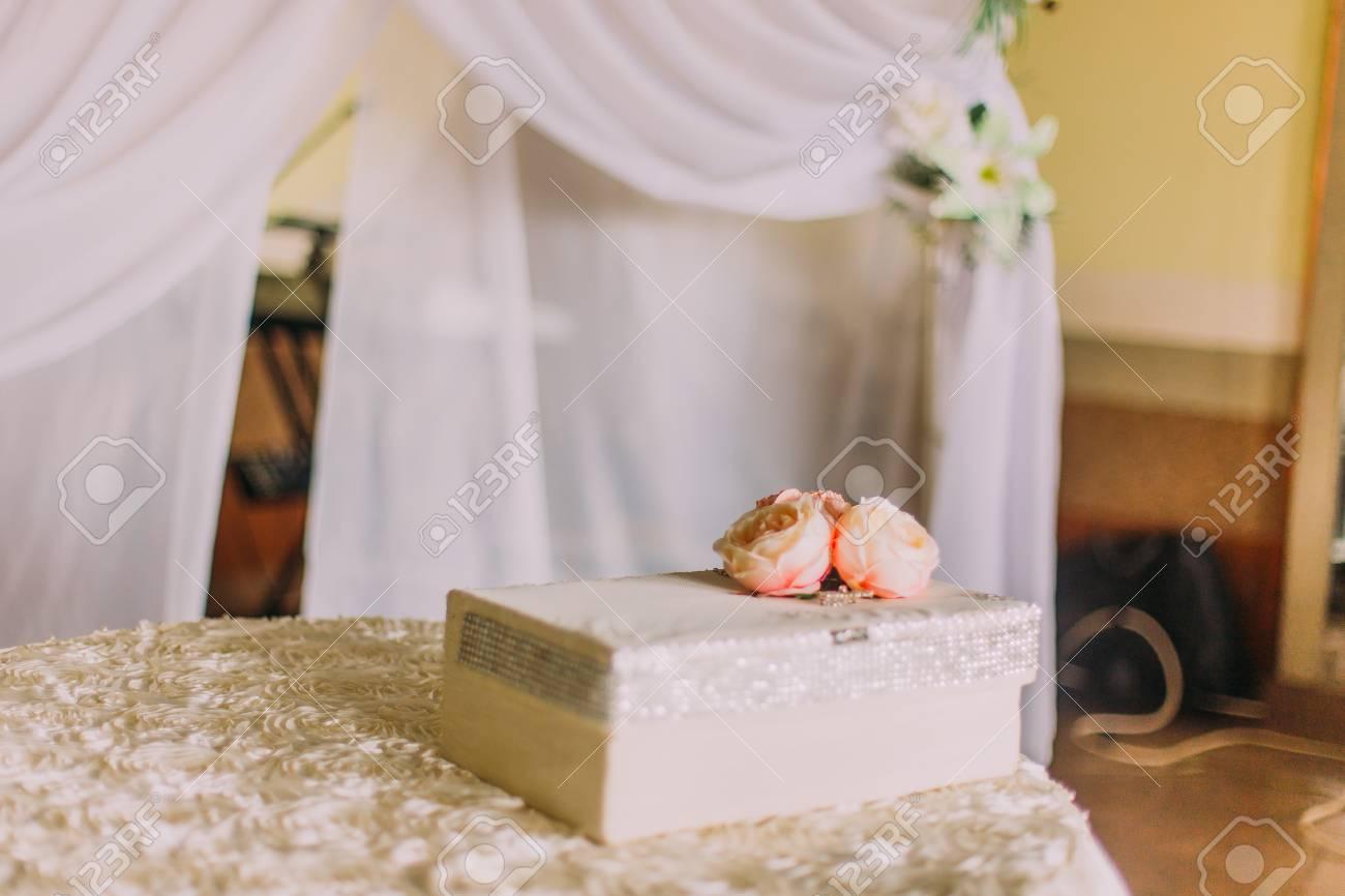 Grote Witte Tafel : Bos van oranje verse rozen met grote witte huidige doos op tafel