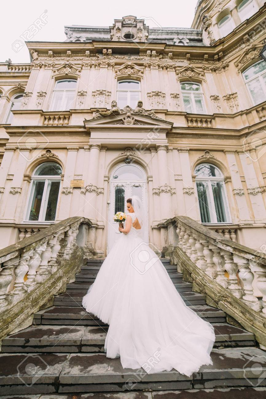 Beautiful Bride In Wedding Dress With Long Train Standing Back ...