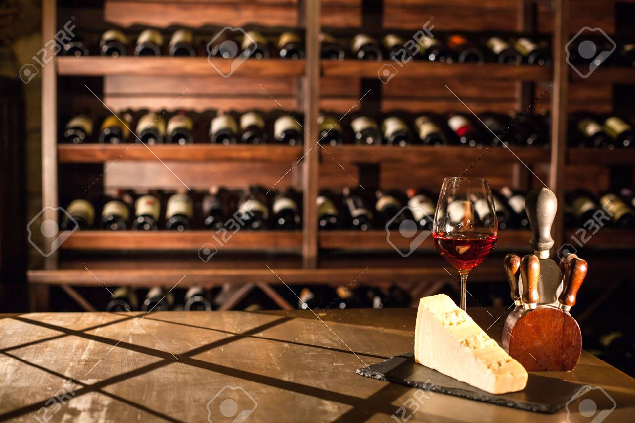 Composition in wine vault. Wine glass, cheese and accessories on a wooden table. Stock Photo - 73526615