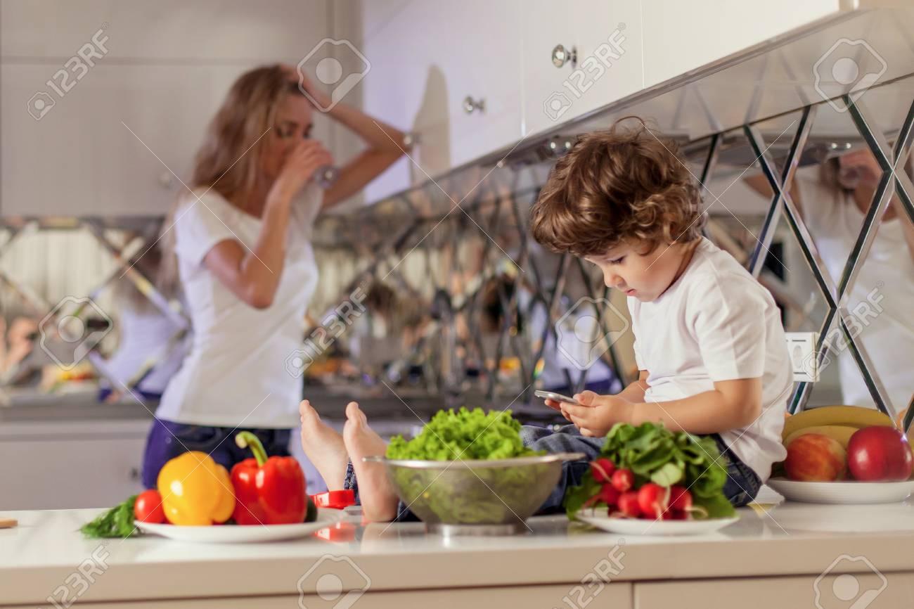 Petit garçon mignon assis sur la surface de la cuisine avec le téléphone  entre ses mains avec sa mère pleurant sur le fond.
