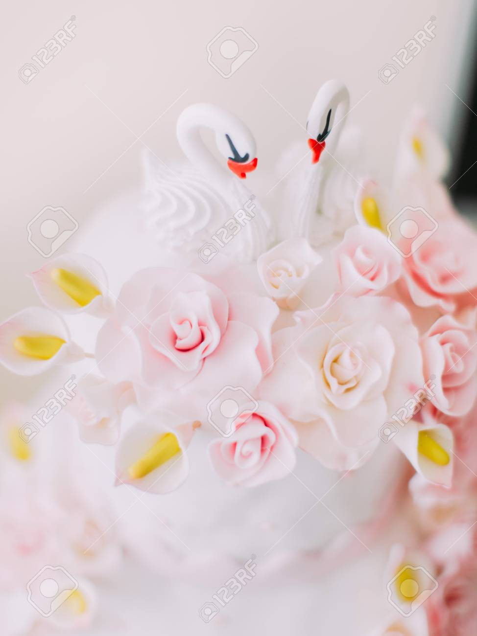 The little swans decorate the white wedding cake with pink flowers stock photo the little swans decorate the white wedding cake with pink flowers mightylinksfo