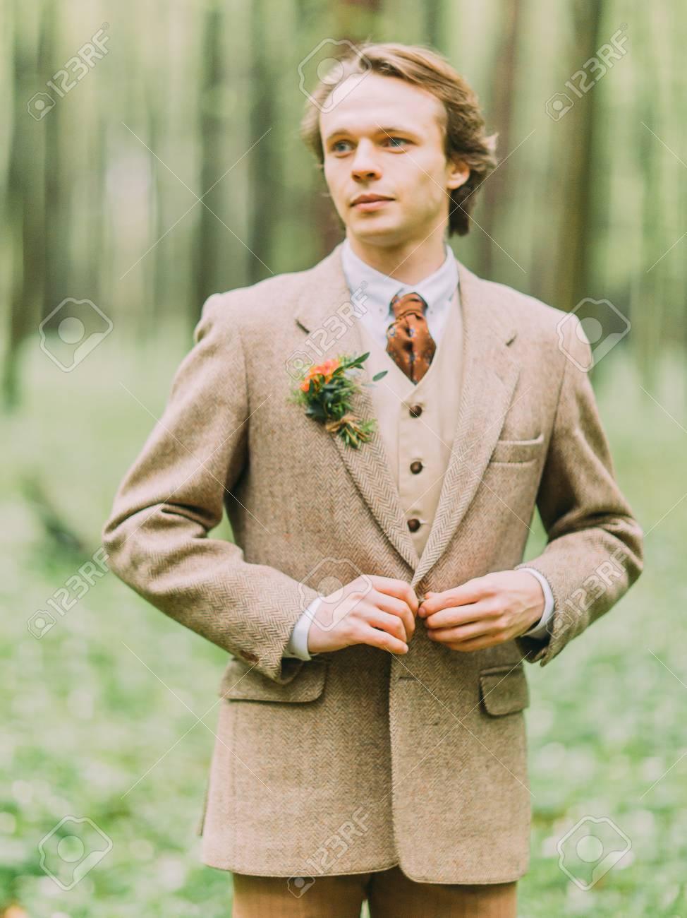 Il ritratto dell'uomo biondo bello nel vestito dell'annata è l'abbottonatura di una giacca d'oca decorata con il mini bouquet.