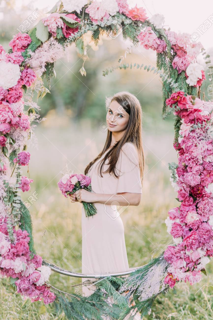 The side vertical portrait of the beautiful bridesmaid holding stock photo the side vertical portrait of the beautiful bridesmaid holding the pink flowers and standing behind the wedding peonies arch at the background izmirmasajfo