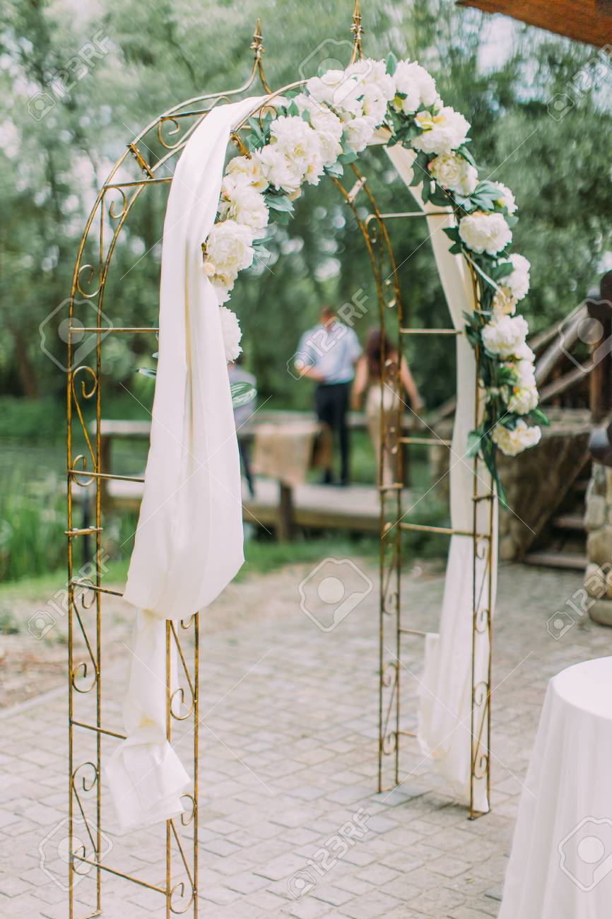 The Side View Of The Wedding Arch Decorated With White Flowers Stock