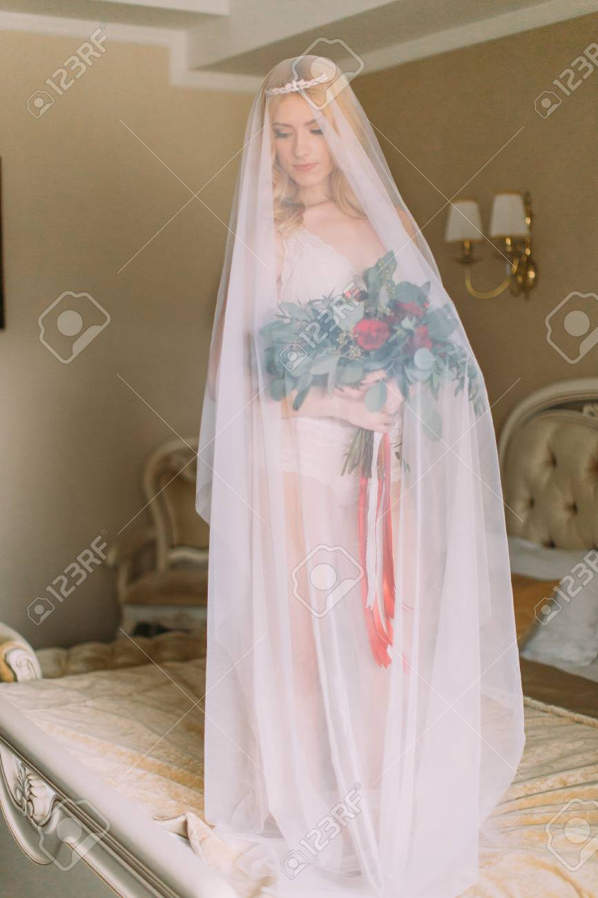 bc8568d9e0d Blonde bride with long veil dressed in sexy white underwear standing on the  bed and holding