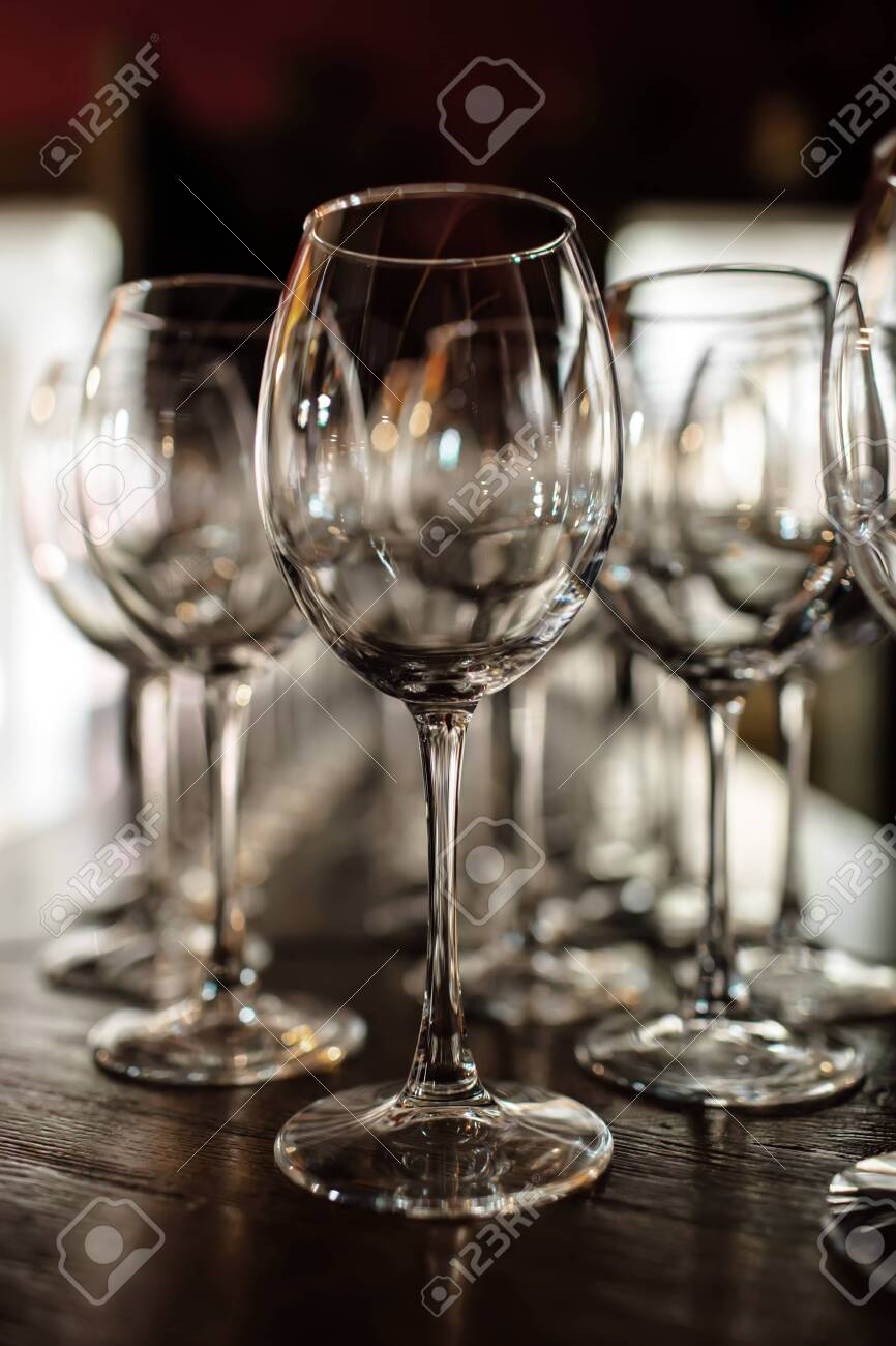empty wine glasses. Beautiful new glasses for wine from glass stand in even rows on a wooden table in a restaurant. selective focus - 130666945