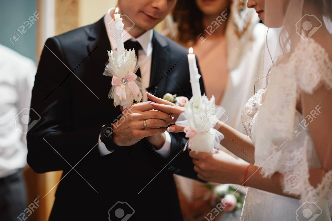 The bride's hand wears an engagement gold ring on the groom's finger. Wedding day. Hands with wedding rings. Close up. - 135818867