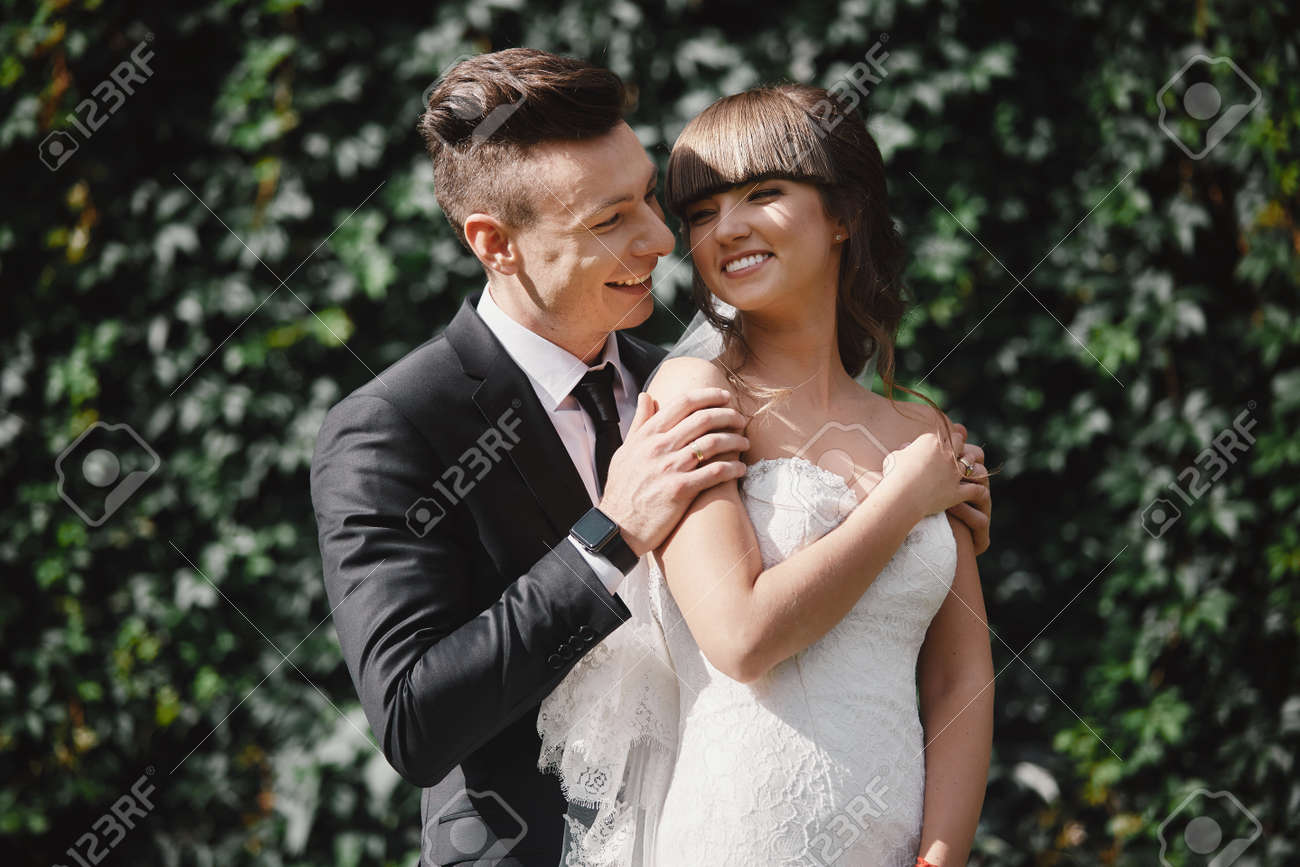 Amazing smiling wedding couple. Pretty bride and stylish groom. groom and bride posing in front wall with green ivy. - 138819867