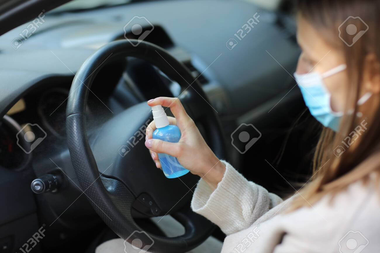 Spraying anti-bacterial sanitizer spray on hand in car, infection control concept. Sanitizer to prevent Coronavirus, Covid-19, flu. Spray bottle. womanwearing in medical protective mask driving a car - 143390046