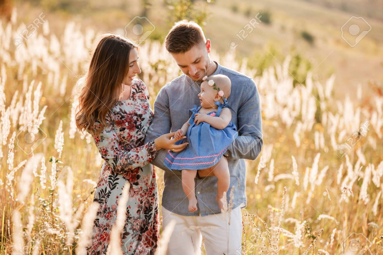 mom, dad and little girl having fun outdoors in the grass on summer day. mothers, fathers and babys day. Happy family for a walk. - 147698434