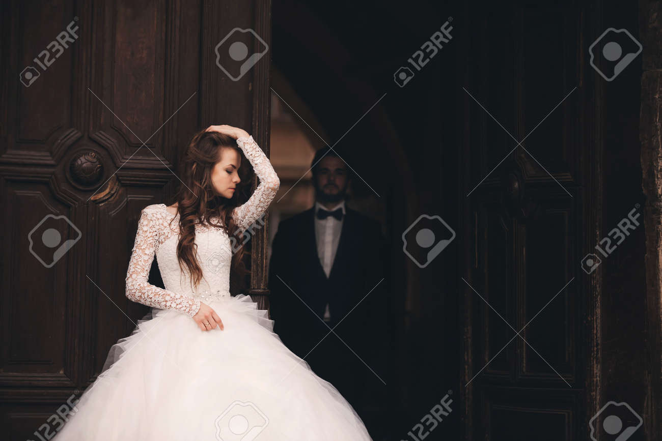 Wedding couple hugs near the vintage green door. Stone walls in ancient town background. bride with long hair in lace dress and groom in suit and bow tie. Tender embrace. Romantic love - 152951110
