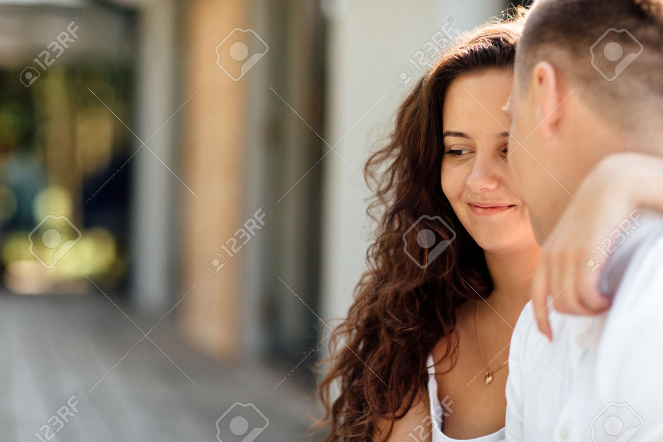 Smiling couple having fun in the park. Love and tenderness, dating, romance, lovers enjoy each other in the summer park. man carry on his back the beautiful curly hair woman smiling and laughing - 165636887