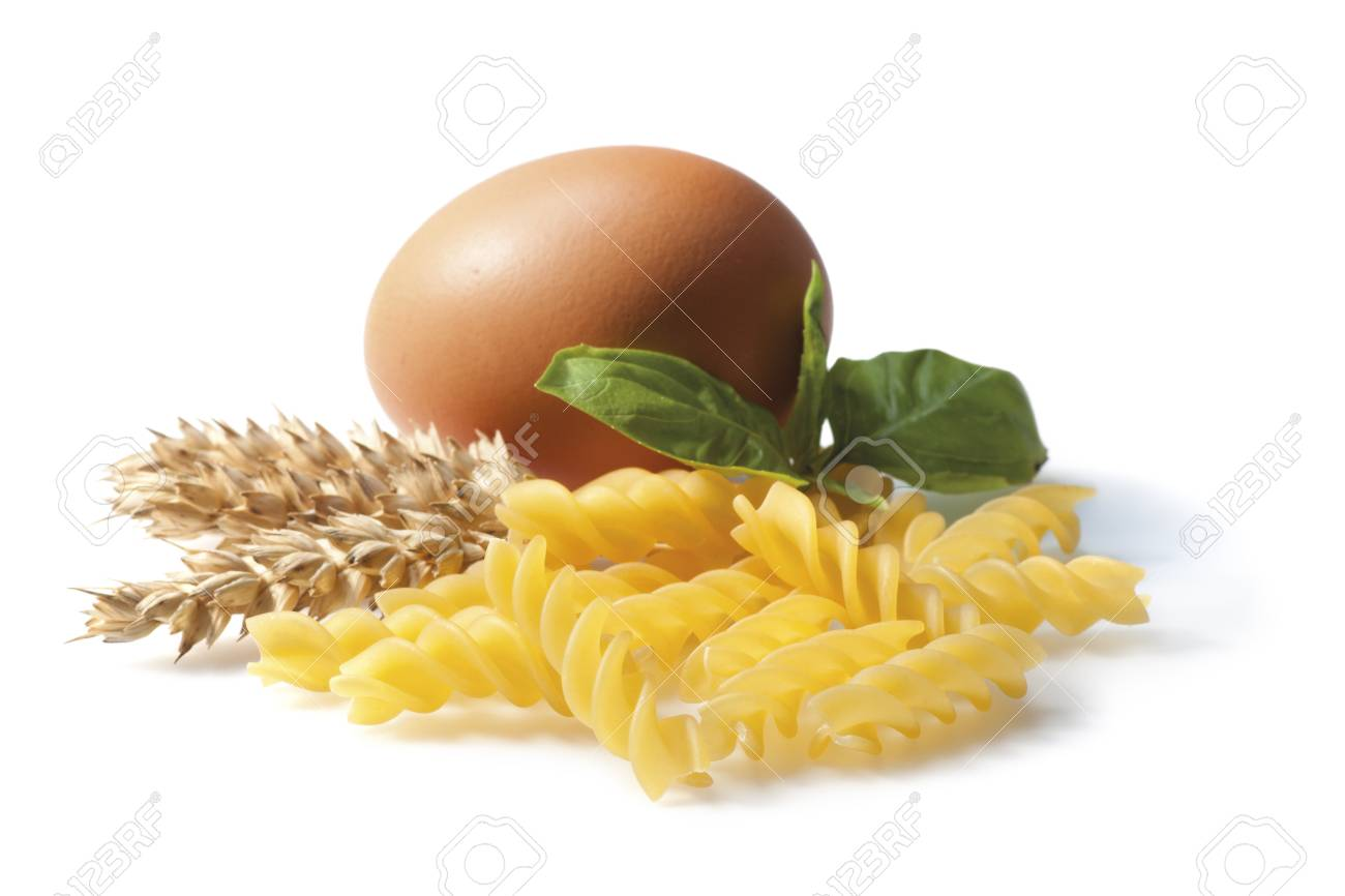 Composition with Fusilli pasta, wheat ears, egg and basil  Isolated on white  Still life  Focus on foreground Stock Photo - 18190261
