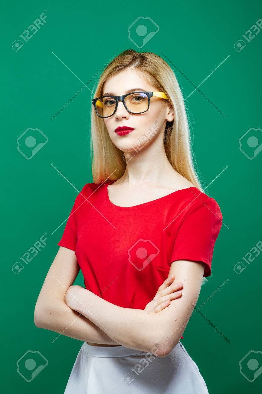 77754c5a2 Portrait of Seriuos Girl Wearing Eyeglasses, Red Top and White Skirt on  Green Background.