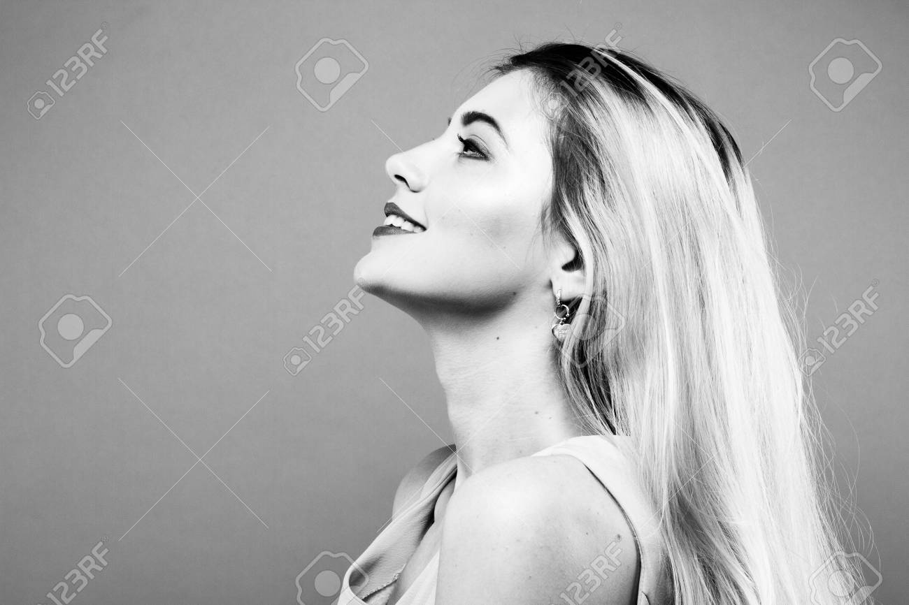 Black and white portrait of attractive smiling girl with long blond hair on blue background