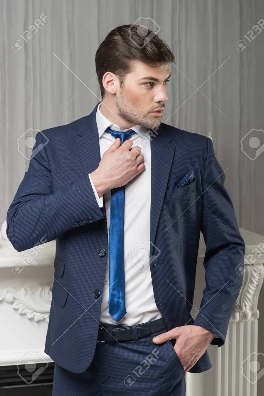 1a98fb1b6a98 Man model in dark blue suit, tie and white shirt near fireplace Stock Photo  -