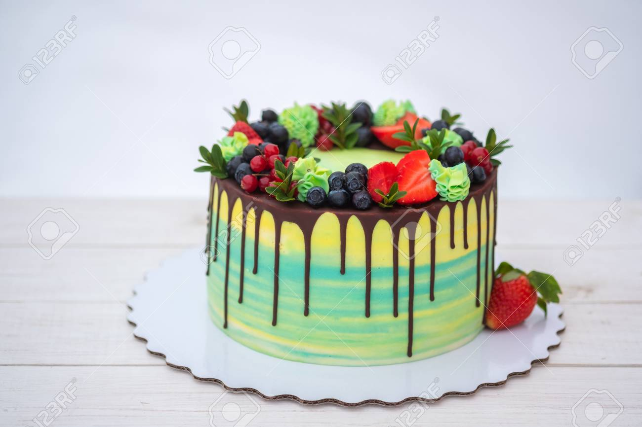 beautiful birthday cake with fresh strawberries, currants and