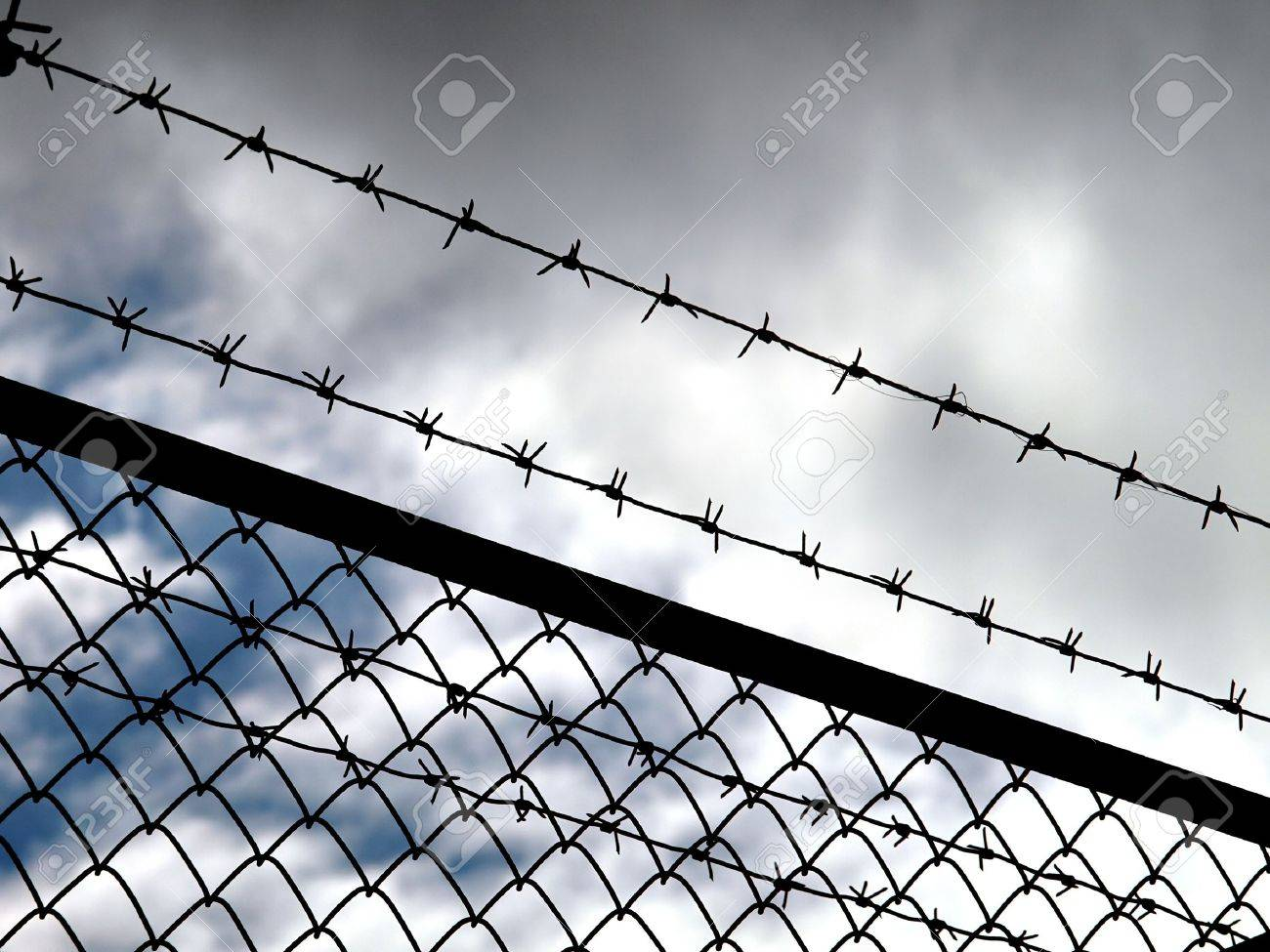 Barbed wire fence with dark clouds in background - imprisonment concept Stock Photo - 4754286