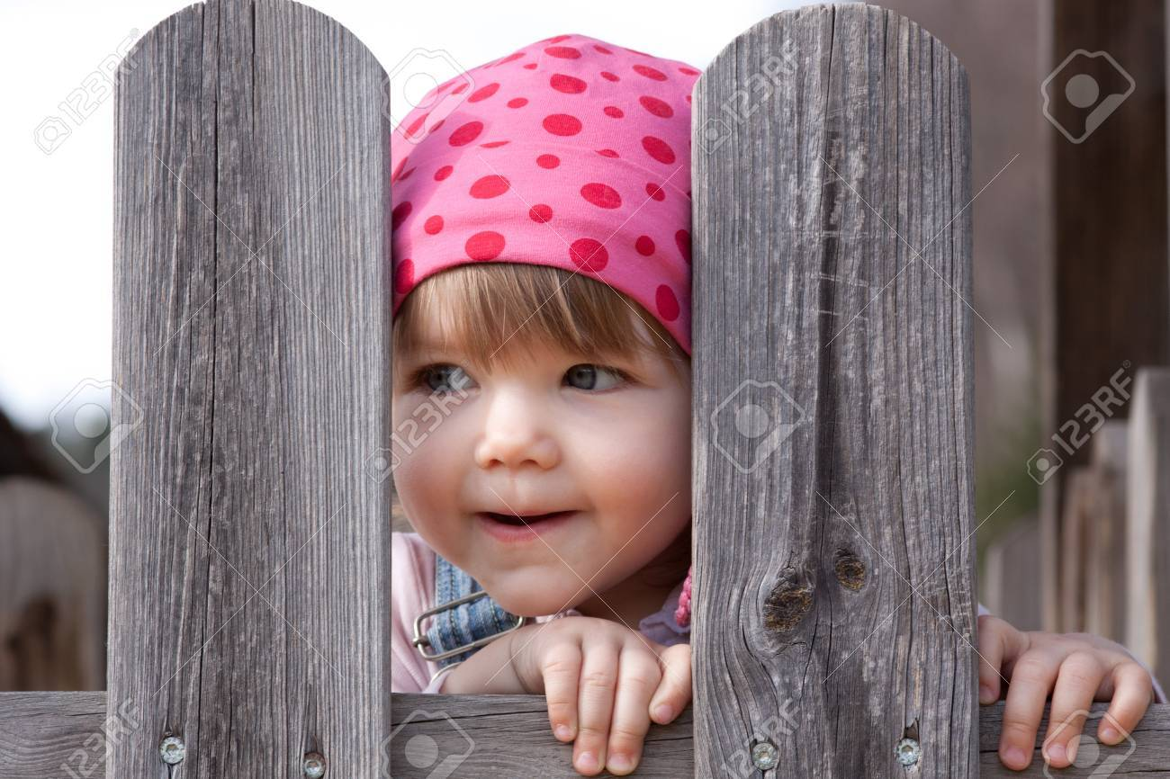 little sweet girl with scarf behind a wooden fence Stock Photo - 12293012