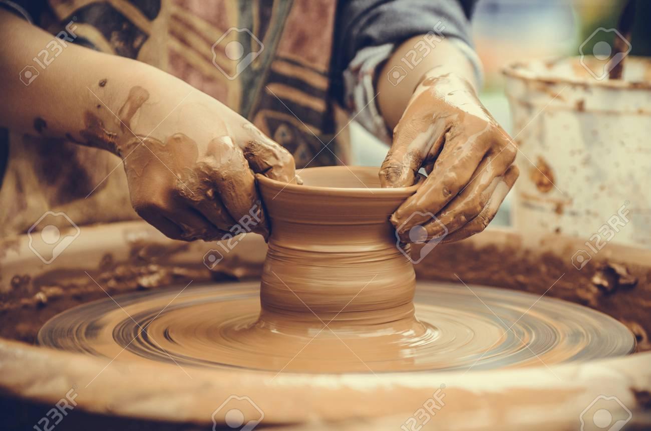 Potter making ceramic mug on the pottery wheel
