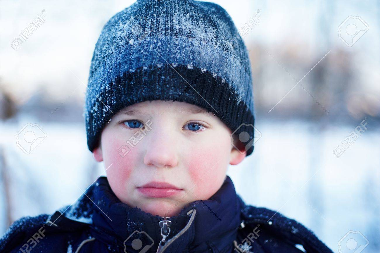 Stock photo the sad crying boy with blue eyes in winter clothes