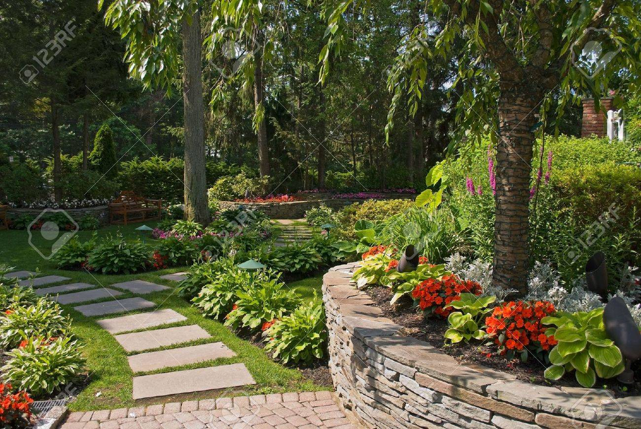 A Summer View Of An Ornamental Garden With A Slate Pathway And Garden Wall  Made Out