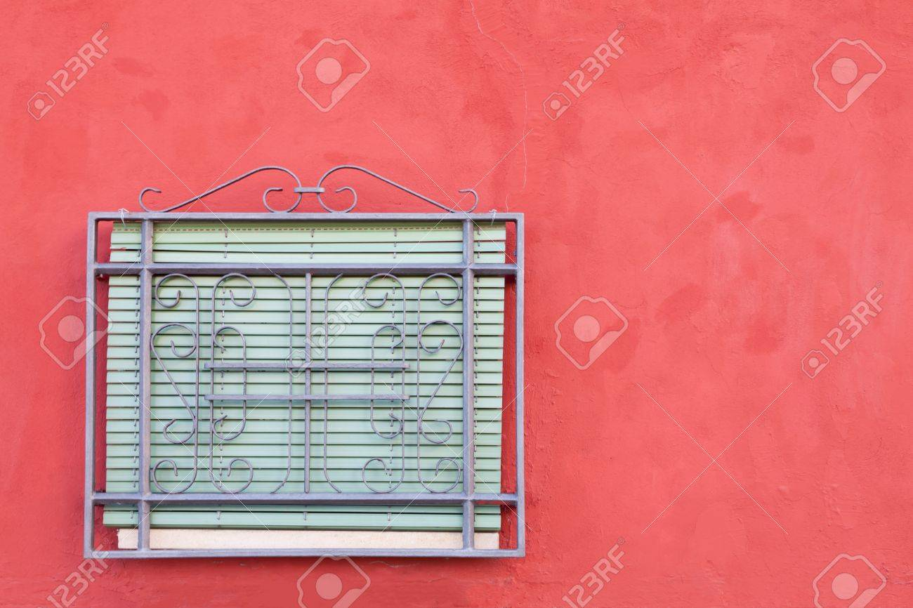 Fenstergitter und roten fensterläden auf weiß getünchte wand ...