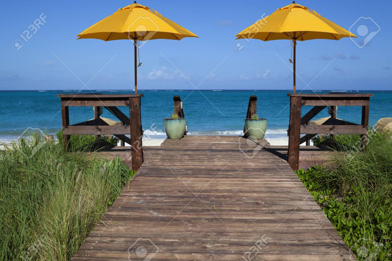 Deck that leads to a tropical blue beach and ocean with two yellow umbrellas Stock Photo - 12028492