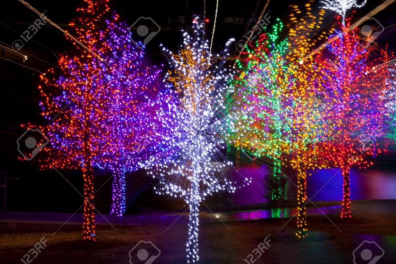 8a52166234d Resumen De árboles Bien Envueltos En Luces LED Para Las Vacaciones De  Navidad Se Refleja En El Lago. Cada árbol Está Envuelto En Un Color.