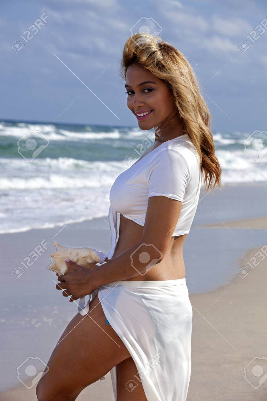 3b3cd26291 Beautiful woman walking on beach in a sexy white outfit carrying a seashell  Stock Photo -