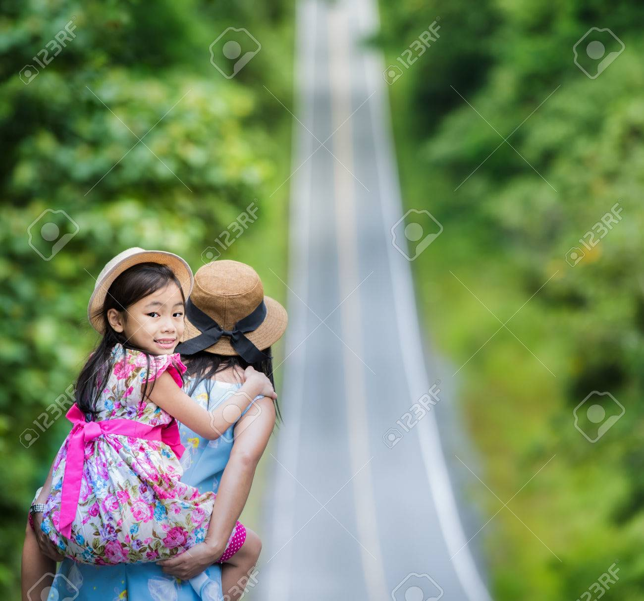 Small happy girl enjoying a piggyback ride on his mothers back and walk on the road. Standard-Bild - 30999900