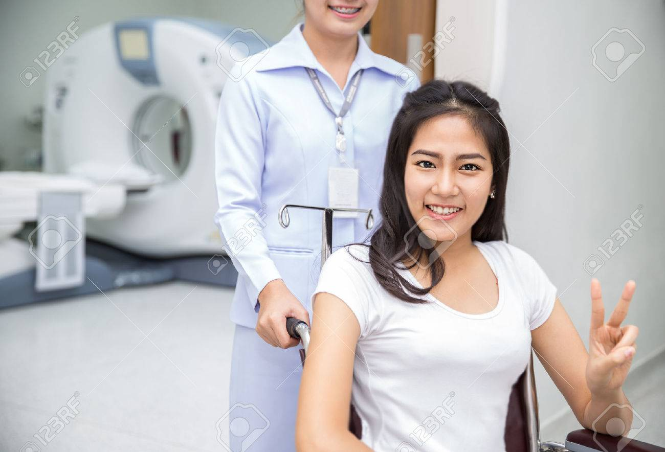 Asian lady sit on wheelshair after exam her body by a CT Scan with nurse Standard-Bild - 32749679